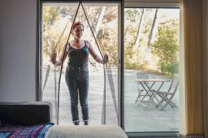 femme entrant dans une maison en ouvrant une moustiquaire sur-mesure aimantée pour baie vitrée Tranquilisafe