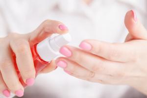mains de femmes qui tiennent un flacon de lotion anti-moustique