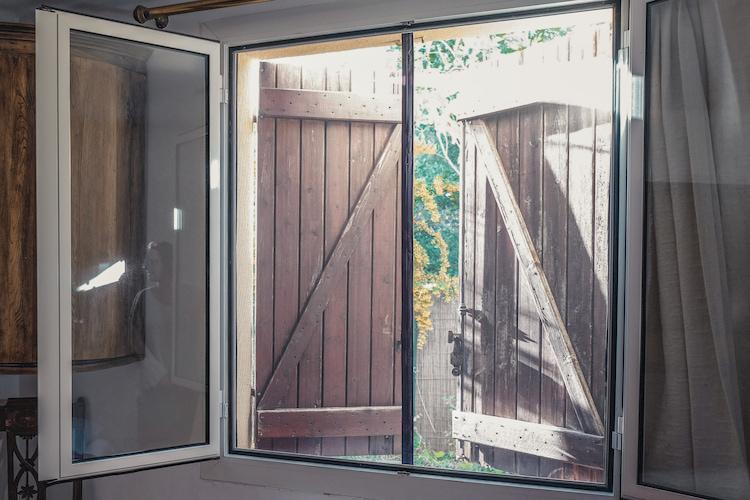 fenêtre ouverte avec  volet en bois et moustiquaire Tranquilisafe