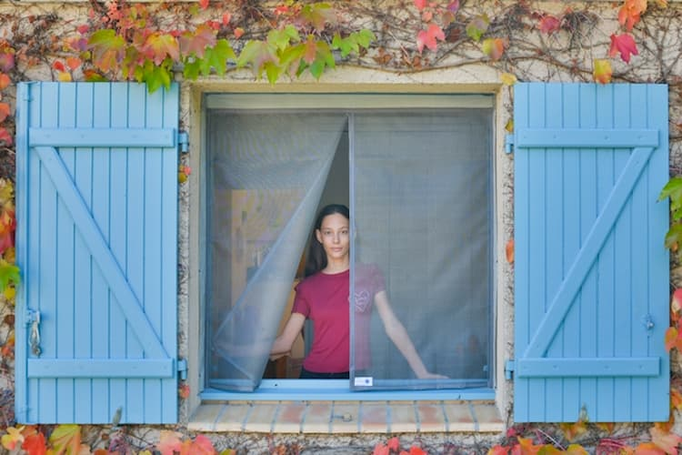 Femme se tenant devant une moustiquaire ajustable pour fenêtre Tranquilisafe