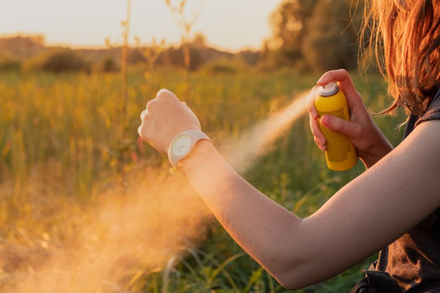 Femme qui s'asperge de spray anti-moustique sur le bras