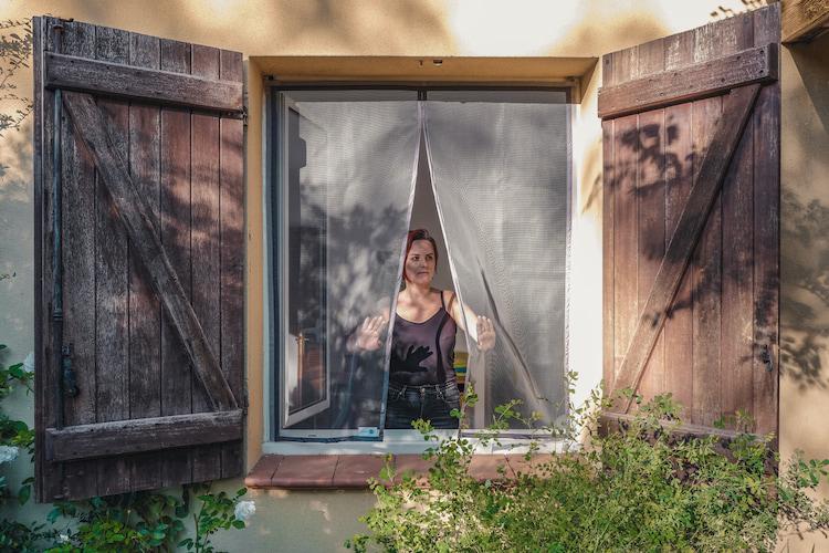 femme se tenant devant une fenêtre avec moustiquaire Tranquilisafe