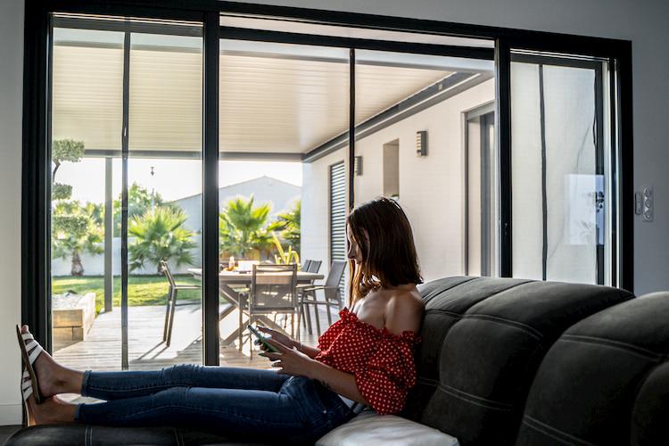 femme allongée dans un canapé devant une baie vitrée avec une moustiquaire Tranquilisafe