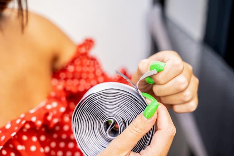 mains de femme qui tiennent une bande velcro de moustiquaire ajustable Tranquilisafe