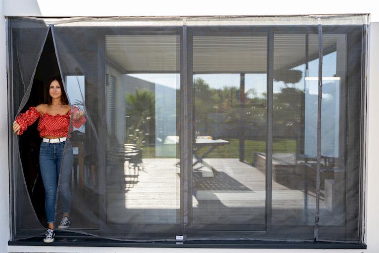 femme en rouge qui sort par une moustiquaire pour baie vitrée Tranquilisafe