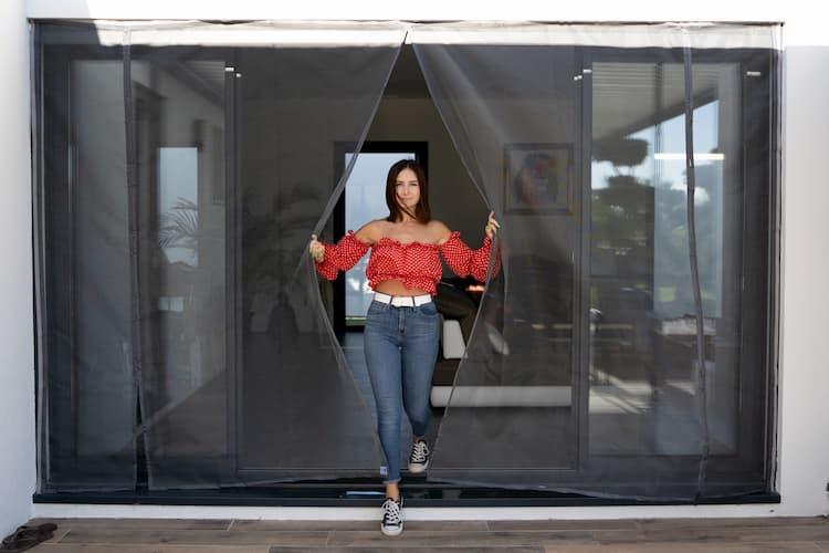 femme ouvrant une moustiquaire ajustable tranquilisafe pour baie vitrée