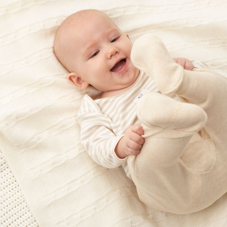 bébé allongé avec manches longues et pantalon contre les moustiques