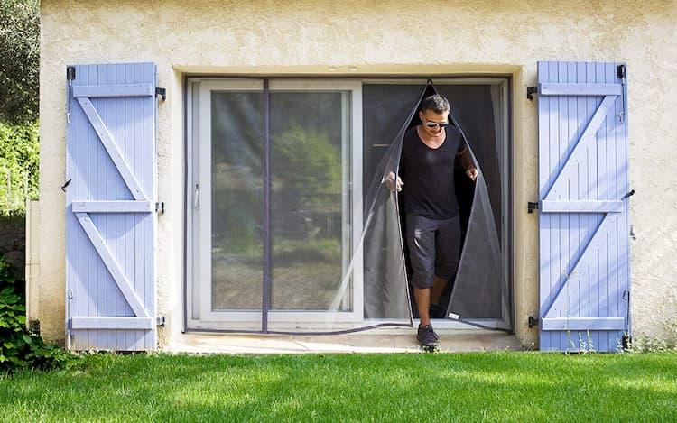 homme en noir qui sort par une moustiquaire pour baie vitrée tranquilisafe