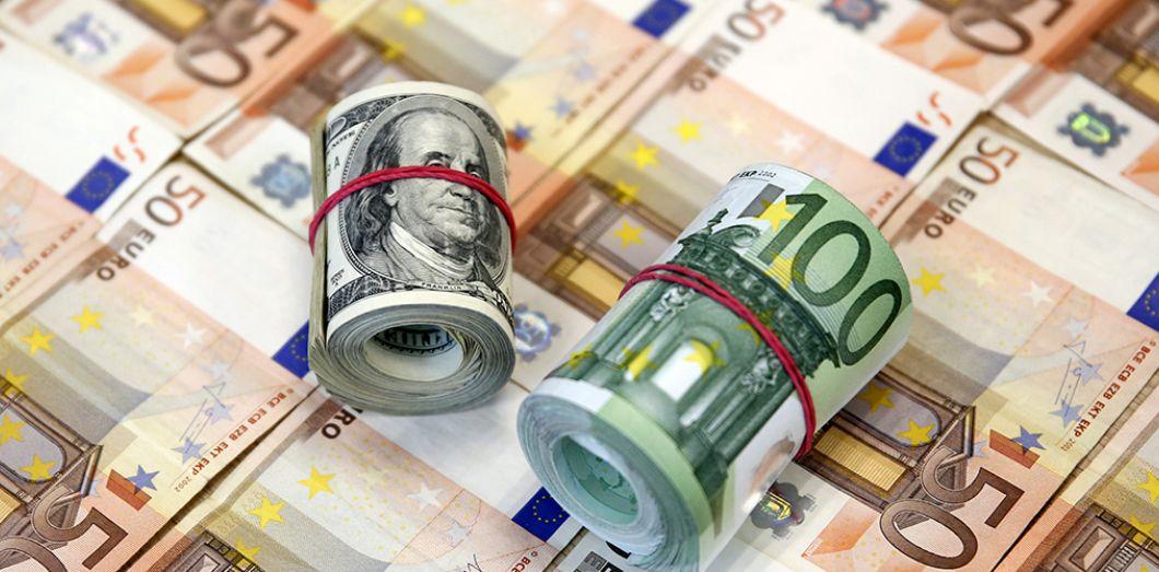 liasses de billets enroulées sur des billets euro
